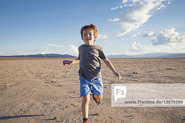 Portrait of happy boy running on arid landscape