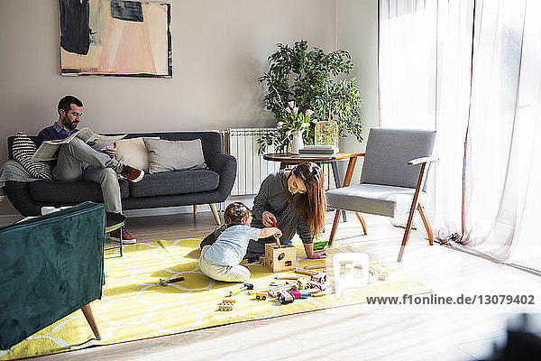 Man reading newspaper while mother playing with son at home
