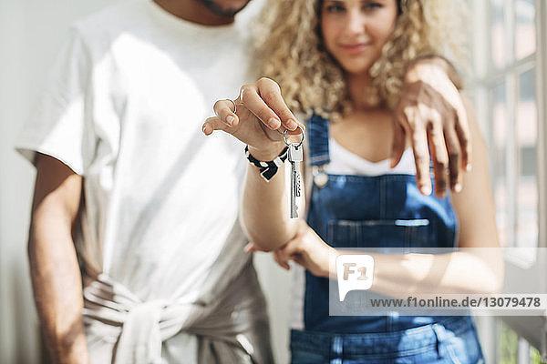 Porträt einer Frau mit Schlüssel in der Hand  die mit ihrem Mann am Fenster im Haus steht