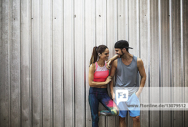 Happy couple standing against metallic wall