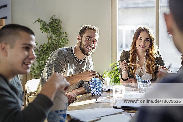 Glückliche Freunde essen  während sie im Klassenzimmer am Tisch sitzen