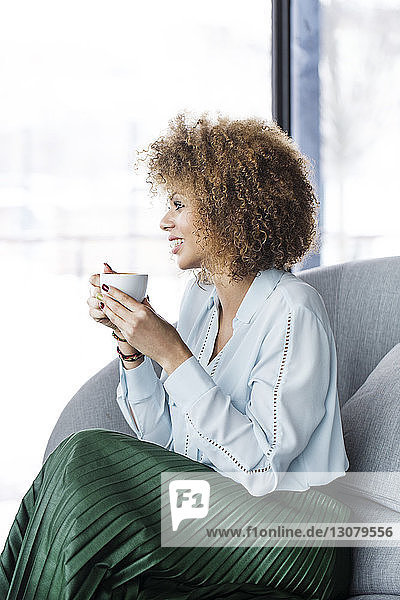 Businesswoman having coffee while sitting on sofa at restaurant