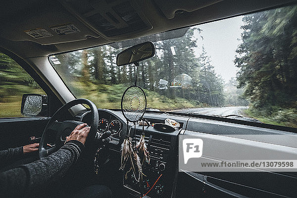 Cropped hands of man driving car on road amidst forest