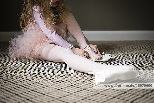 Girl wearing shoe while sitting on carpet at home