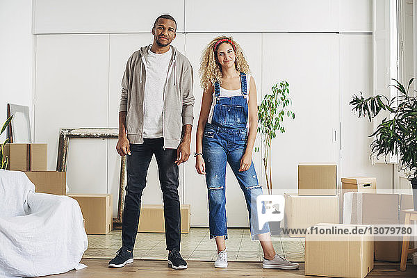 Portrait of smiling couple standing at new home