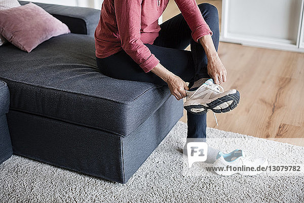 Low section of mature woman wearing sports shoe at home