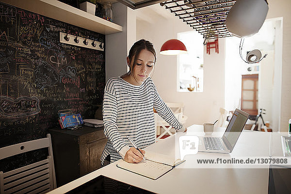 Woman writing in diary while working on laptop at home