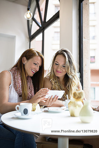 Happy female friends using mobile phone at cafe table