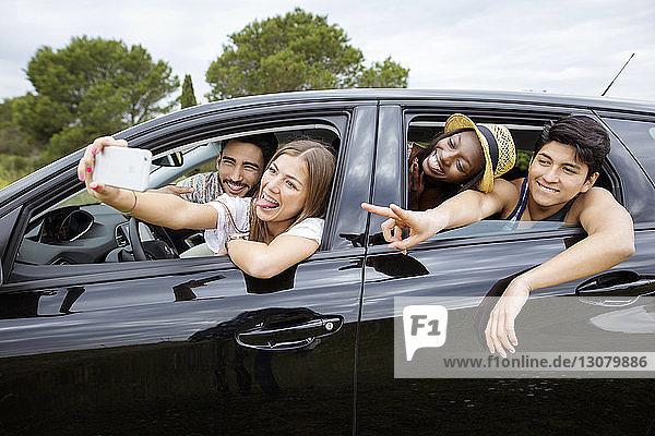 Fröhliche männliche und weibliche Freunde  die im Auto sitzen