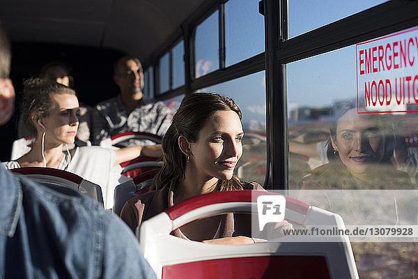 Fahrgäste  die während der Fahrt im Reisebus durch das Fenster schauen