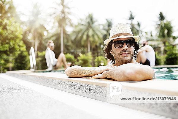 Nachdenklicher Mann entspannt sich im Schwimmbad mit Freunden im Hintergrund