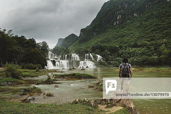 Rückansicht eines Mannes mit Rucksack  der einen Wasserfall betrachtet  während er auf einem Felsen vor bewölktem Himmel steht