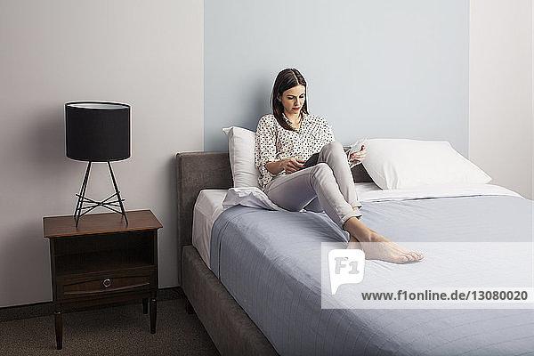 Geschäftsfrau liest Zeitschrift  während sie im Hotelzimmer auf dem Bett sitzt
