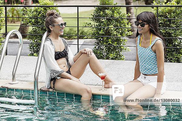 Glückliche Freundinnen entspannen sich am Pool
