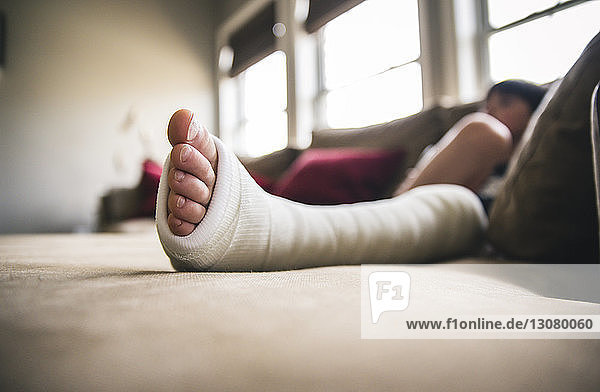 Close-up of boy with fractured leg sitting on sofa at home