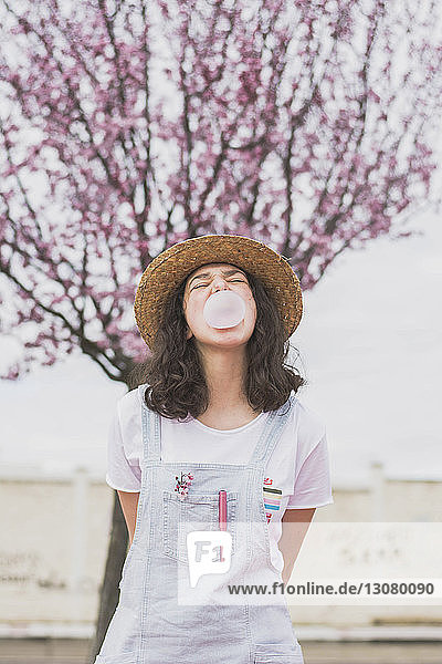 Young woman blowing bubble gum while standing against cherry tree at park