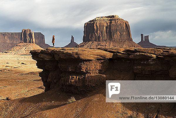Mitteldistanzansicht einer Frau  die an einer Felsformation im Oljato-Monument Valley steht