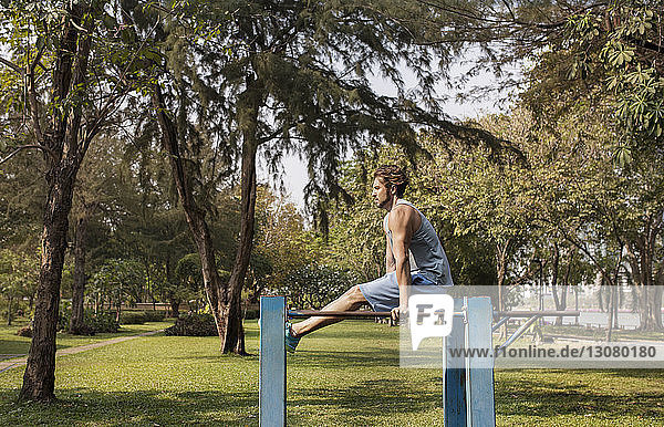 Side view of man exercising on metal rods at grassy field