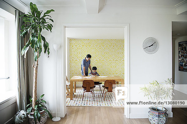 Father assisting boy with homework at home