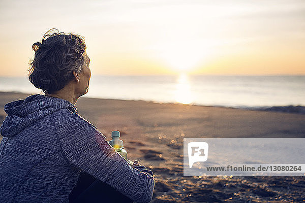 Thoughtful woman with bottle sitting at beach against sky