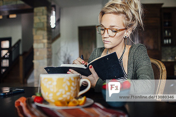 Woman writing diary while sitting at breakfast table