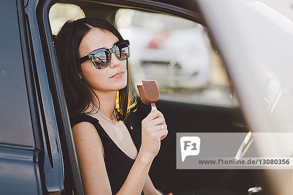 Young woman wearing sunglasses holding frozen sweet food while sitting in car seen through window