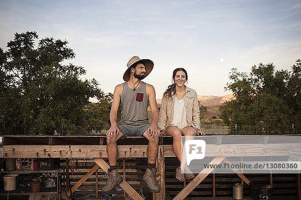 Glückliche Bäuerin sitzt mit Mann auf Holzkonstruktion auf dem Bauernhof