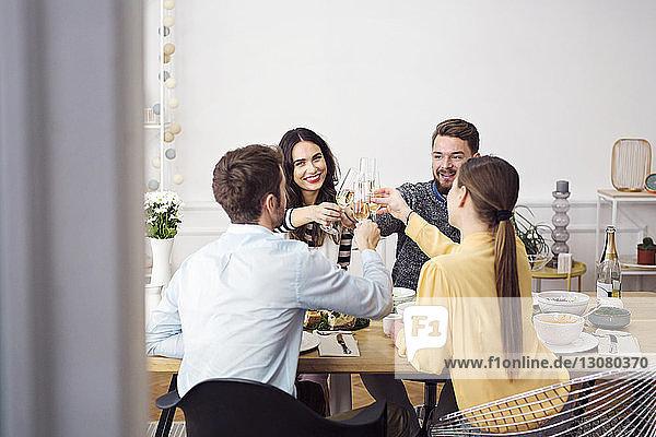 Glückliche Freunde stoßen beim Mittagessen am Esstisch auf Champagnerflöten an