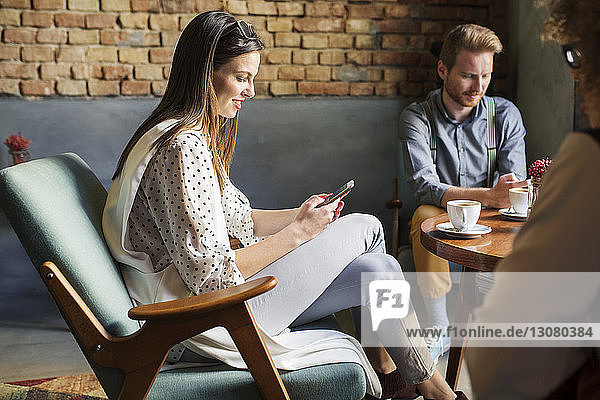 Businesswoman using smart phone while sitting with colleagues at hotel lobby