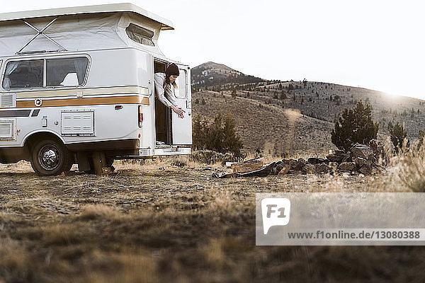 Frau staubt Hände ab  während sie im Wohnmobil auf dem Feld vor klarem Himmel steht