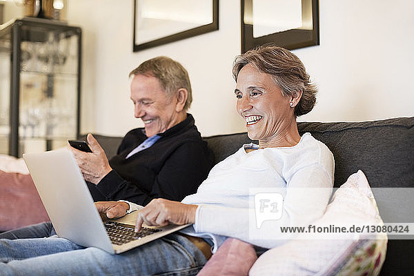 Cheerful senior couple using laptop and smart phone on sofa at home