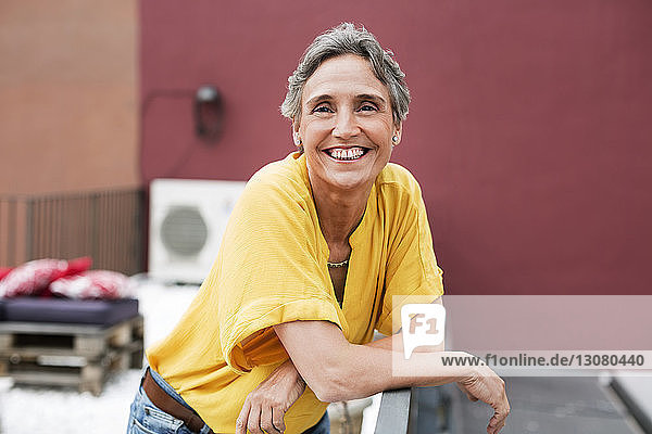 Portrait of happy mature woman standing on terrace