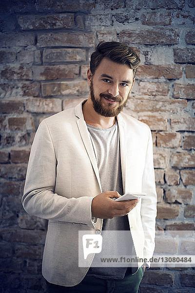 Porträt eines Geschäftsmannes beim Versenden von Textnachrichten  während er im Büro an einer Ziegelmauer steht