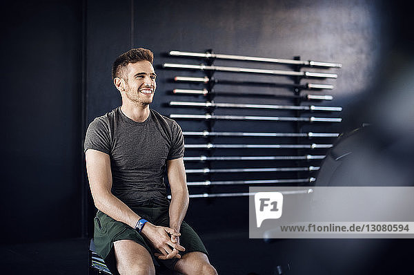 Happy man looking away while sitting on box in gym