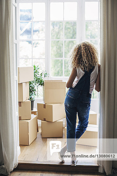 Rear view of woman standing at doorway in new house