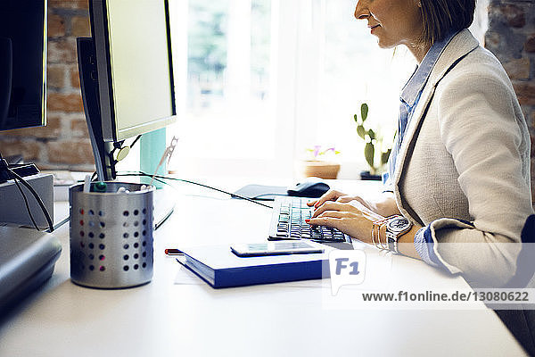 Midsection of businesswoman using computer at desk in creative office