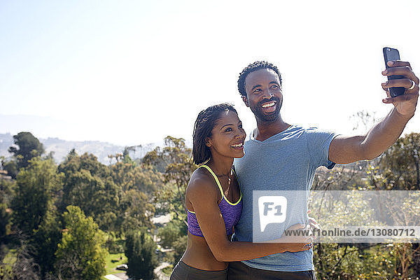 Glückliches Paar  das sich auf dem Spielfeld per Mobiltelefon selbstständig macht
