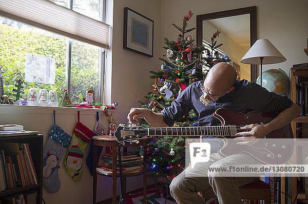 Mann hält zu Weihnachten Gitarre zu Hause