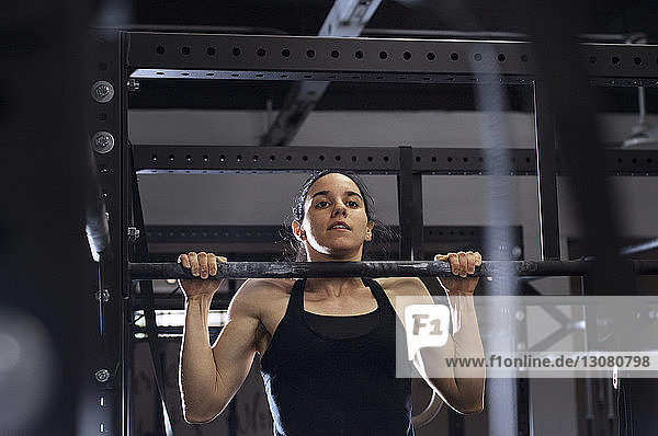 Low angle view of determined sportswoman exercising on monkey bar in gym