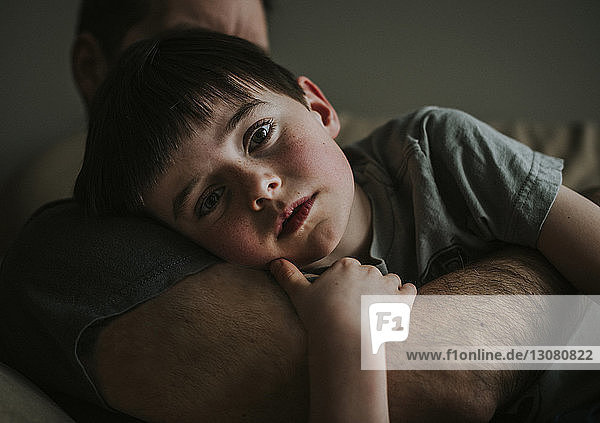 Close-up of father embracing son while lying on sofa at home
