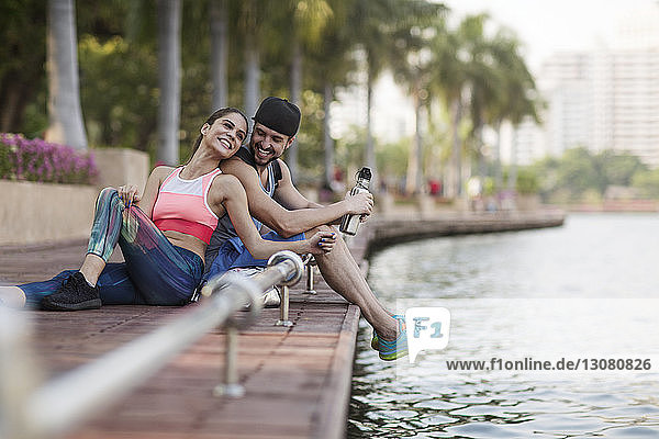 Happy couple sitting and enjoying on wooden walkway at riverbank