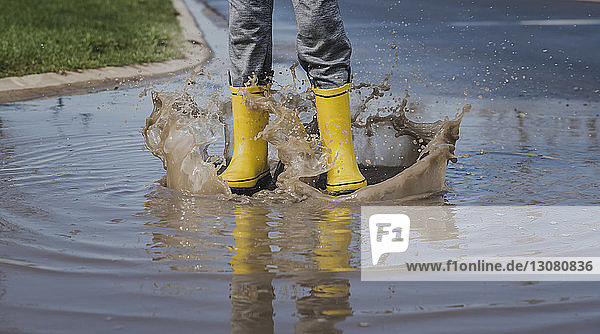 Low section of playful boy wearing yellow rubber boots while jumping in puddle
