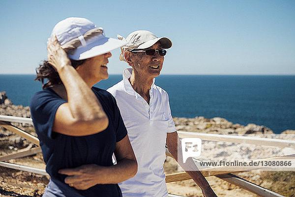 Lächelndes älteres Ehepaar schaut aufs Meer  während es an der Reling gegen den klaren Himmel steht