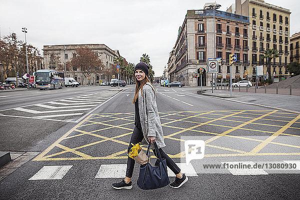 Porträt einer Frau  die einen Blumenstrauss in einer Tasche trägt  während sie auf der Strasse der Stadt geht
