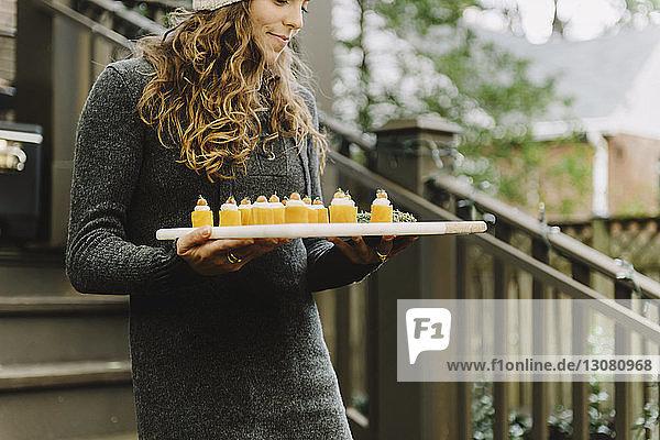 Woman carrying appetizer on board in backyard