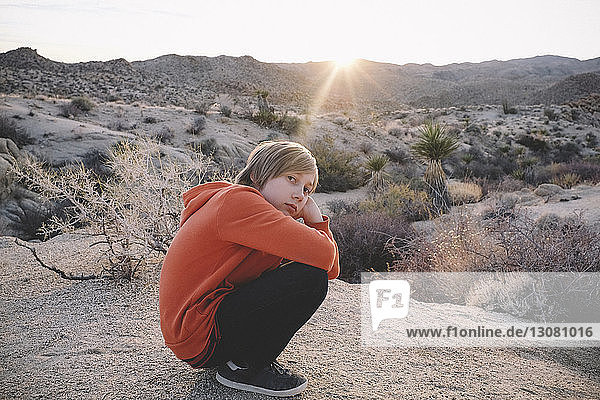 Portrait of boy crouching on rock formation at Joshua Tree National Park against sky during sunset