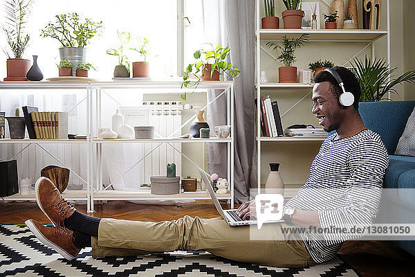 Side view of happy man using laptop while sitting on floor in living room