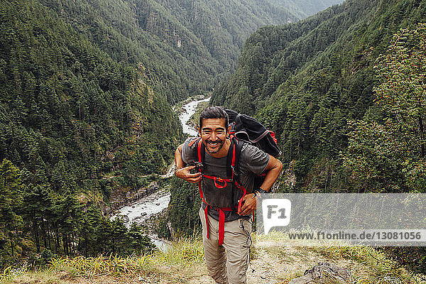Male hiker with backpack standing on mountain at Sagarmatha National Park