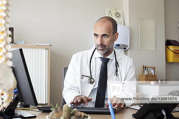 Arzt benutzt Desktop-Computer  während er im Krankenhaus am Tisch sitzt