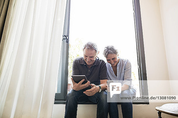 Senior couple using smart phone and tablet computer while sitting on window sill at home